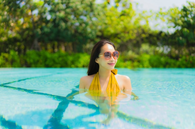 Portrait beautiful young asian woman smile happy relax and leisure in the swimming pool Free Photo