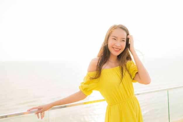 Portrait beautiful young asian woman smile happy and relax at outdoor balcony with sea beach and oce Free Photo