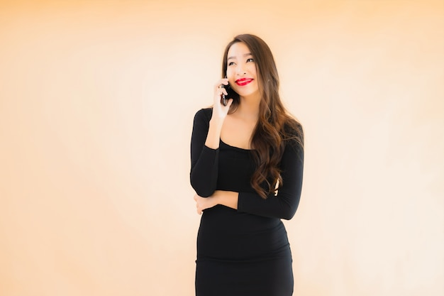肖像画の美しい若いアジアの女性の笑顔幸せな使用スマート携帯電話 無料写真