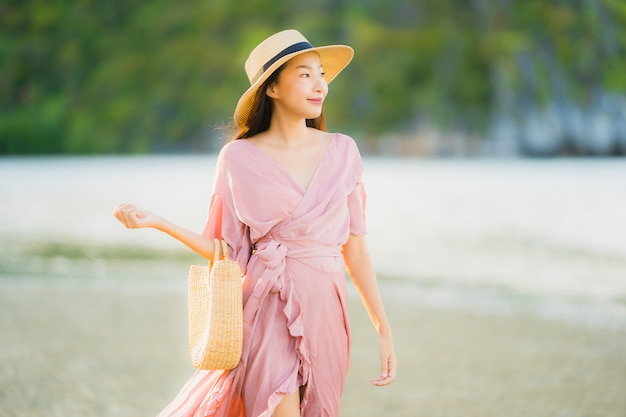Portrait beautiful young asian woman smile happy walk on the tropical outdoor nature beach sea Free Photo