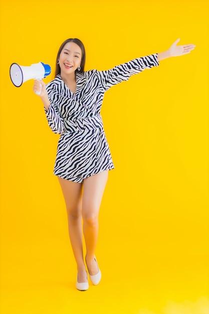 肖像画の美しい若いアジア女性は黄色のメガホンに満足して笑顔します。 無料写真