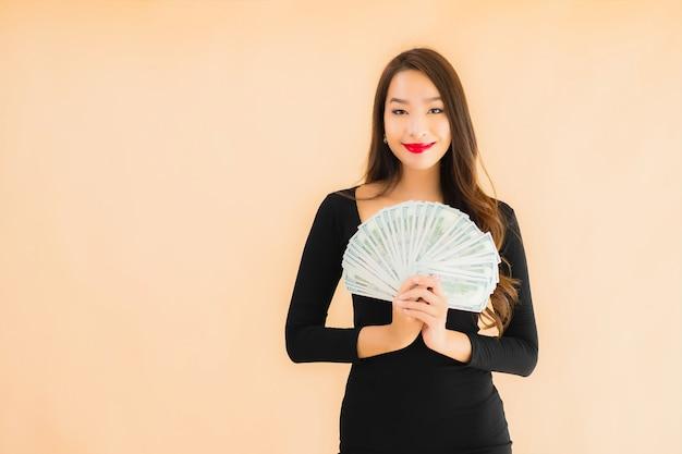 肖像画の美しい若いアジア女性はお金と現金で幸せな笑顔 無料写真