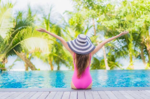 Улыбка женщины портрета красивая молодая азиатская ослабляет вокруг открытого бассейна в курортном отеле на отключении перемещения каникул праздника Бесплатные Фотографии