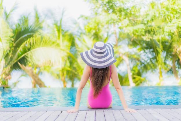 肖像画美しい若いアジアの女性の笑顔は、休日の休暇旅行旅行でリゾートホテルの屋外スイミングプールの周りでリラックス 無料写真