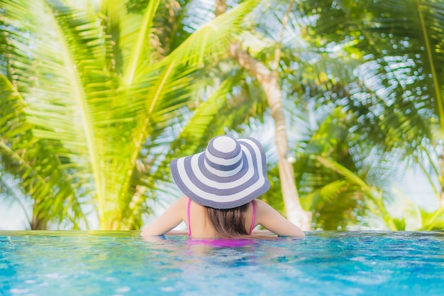 Portrait beautiful young asian woman smile relax around outdoor swimming pool in resort hotel on holiday vacation travel trip Free Photo