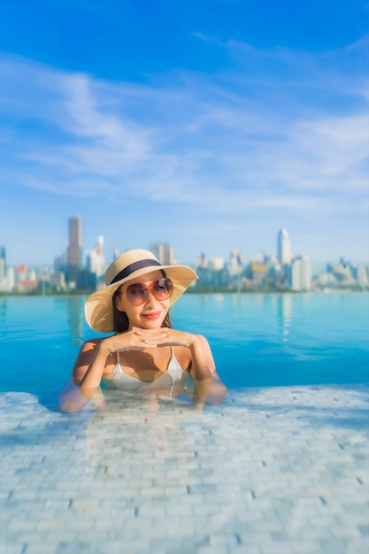 Portrait beautiful young asian woman smile relax leisure around outdoor swimming pool with city view Free Photo