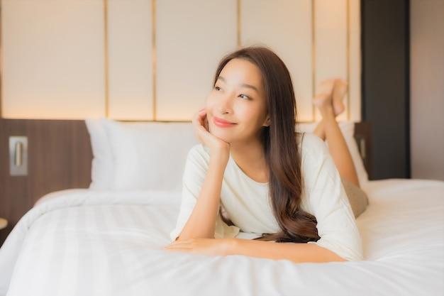 Il sorriso della bella giovane donna asiatica del ritratto si rilassa il tempo libero sul letto nell'interno della camera da letto Foto Gratuite