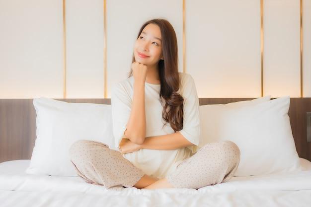 肖像画美しい若いアジアの女性の笑顔は寝室のインテリアのベッドでレジャーをリラックス 無料写真