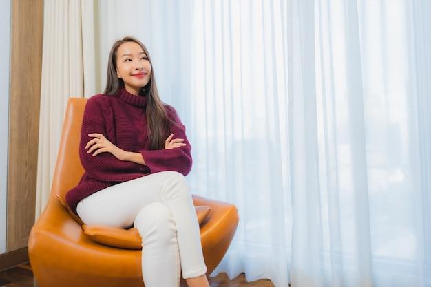 Улыбка женщины портрета красивая молодая азиатская ослабляет на софе в интерьере живущей комнаты Бесплатные Фотографии