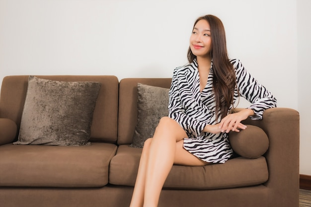 세로 아름 다운 젊은 아시아 여자 미소 거실 인테리어에 소파에 휴식 무료 사진