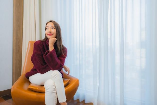 Il bello giovane sorriso asiatico della donna del ritratto si rilassa sul sofà nell'interno del salone Foto Gratuite