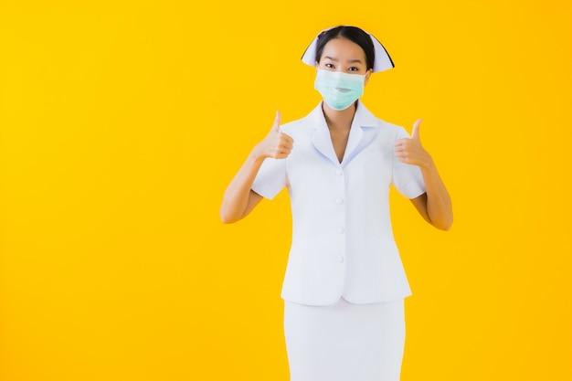 Portrait beautiful young asian woman thai nurse wear mask for protect covid19 or coronavirus Free Photo