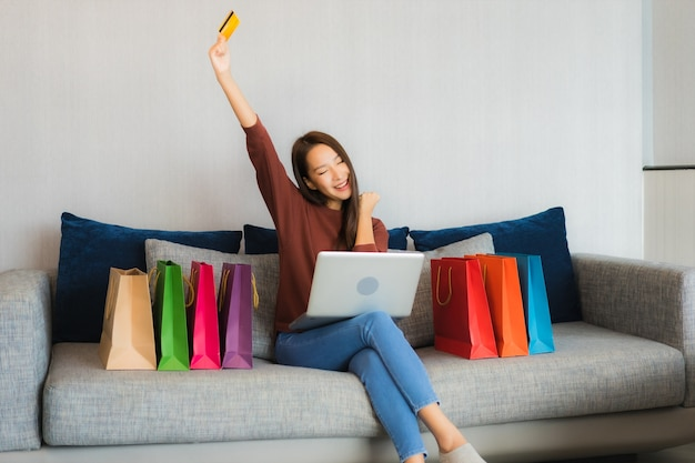 美しい若いアジア女性の肖像画は、リビングルームのインテリアのソファーでオンラインショッピングのためのコンピューターのラップトップとクレジットカードを使用します。 無料写真