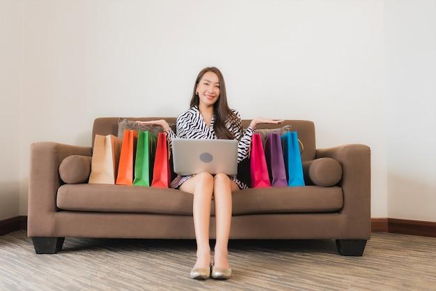 Компьтер-книжка компьютера пользы женщины портрета красивая молодая азиатская, умный мобильный телефон или наличные деньги для онлайн-покупок на софе в интерьере живущей комнаты Бесплатные Фотографии