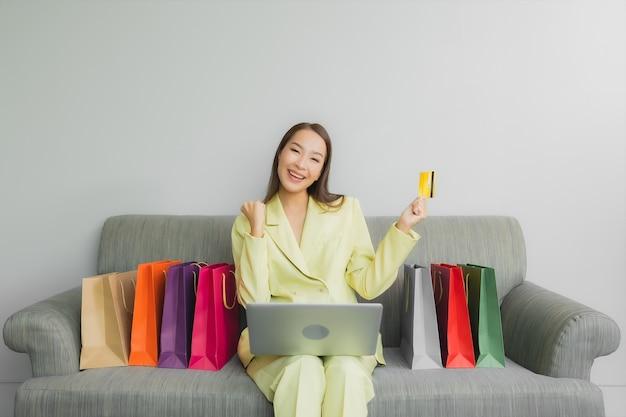 肖像画の美しい若いアジア女性は、リビングルームのインテリアのソファーでオンラインショッピングのためのクレジットカードでコンピューターのラップトップを使用します。 無料写真