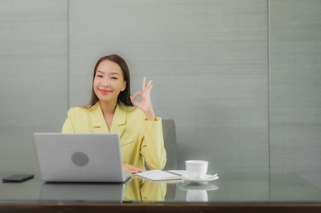 세로 아름 다운 젊은 아시아 여자 인테리어 룸에서 작업 테이블에 스마트 휴대 전화와 컴퓨터 노트북을 사용 무료 사진