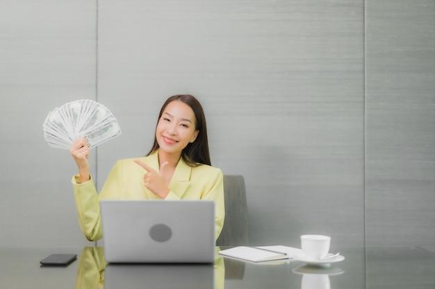 Computer portatile del computer di uso della bella giovane donna asiatica del ritratto con il telefono cellulare astuto sul tavolo di lavoro alla stanza interna Foto Gratuite