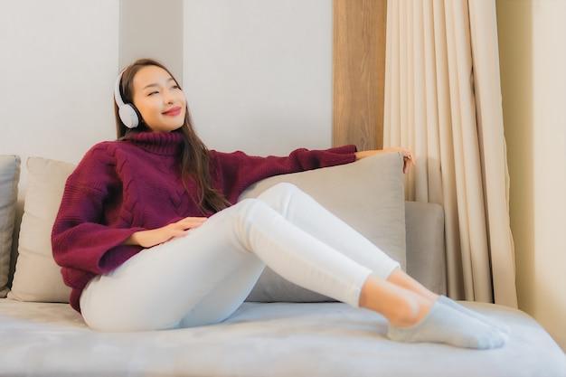 肖像画の美しい若いアジアの女性は、リビングルームのインテリアのソファーで音楽を聴くためのヘッドフォンを使用します。 無料写真