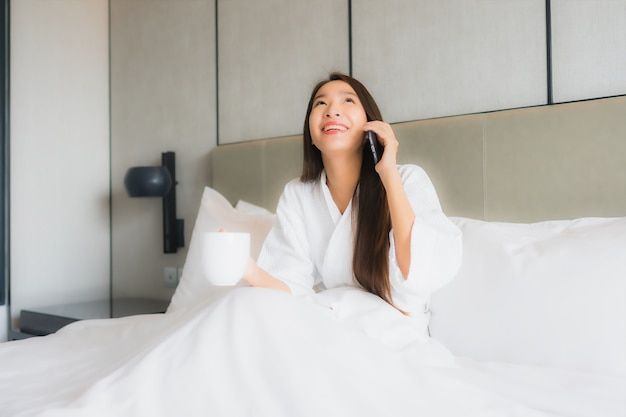 Portrait beautiful young asian woman use smart mobile phone in bedroom Free Photo