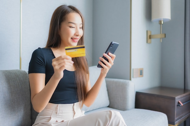 Portrait beautiful young asian woman use smart mobile phone or laptop with credit card on sofa in living room area Free Photo
