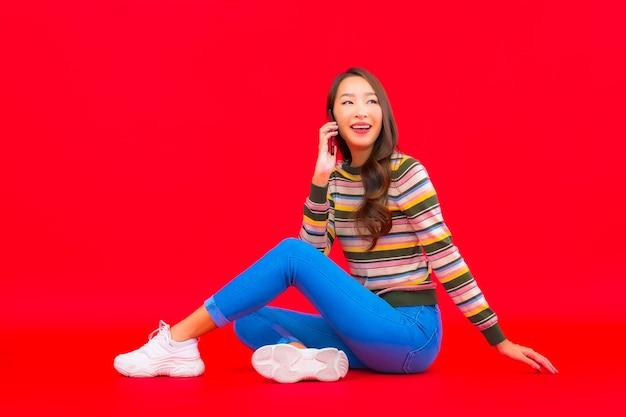 세로 아름 다운 젊은 아시아 여자 빨간색 격리 된 벽에 스마트 휴대 전화를 사용 무료 사진