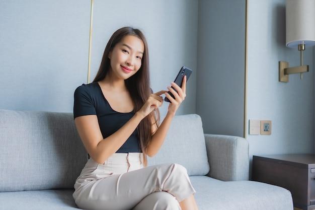 肖像画の美しい若いアジア女性はリビングルームエリアのソファーにスマートな携帯電話を使用します。 無料写真