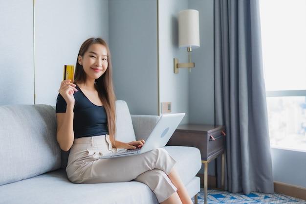 肖像画の美しい若いアジアの女性は、スマートフォンまたはラップトップを使用してリビングルームのソファーにクレジットカードを 無料写真