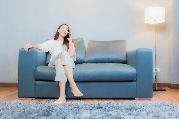 La bella giovane donna asiatica del ritratto utilizza il telefono cellulare astuto sul sofà nell'interno del salone Foto Gratuite