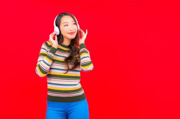 Мобильный телефон пользы женщины портрета красивой молодой азиатской умный с наушниками для слушать музыку Бесплатные Фотографии