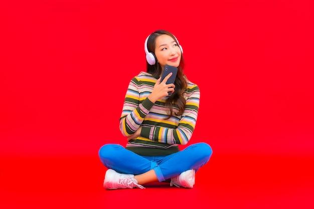 La bella giovane donna asiatica del ritratto utilizza il telefono cellulare astuto con la cuffia per ascoltare la musica Foto Gratuite