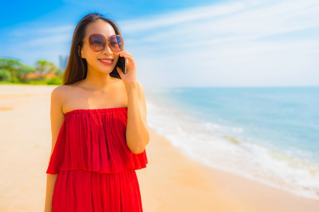 Portrait beautiful young asian woman using cellphone or mobile phone on the beach and sea Free Photo
