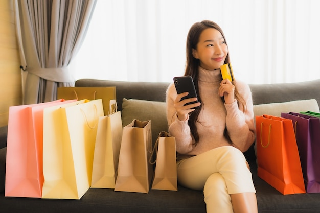 Portrait beautiful young asian woman using laptop or smart mobile cell phone for shopping online on sofa around shopping bag Free Photo