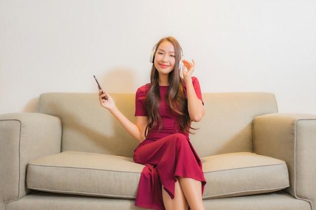 ソファで音楽を聴くためにスマートな携帯電話とヘッドフォンを使用して美しい若いアジアの女性の肖像画 無料写真