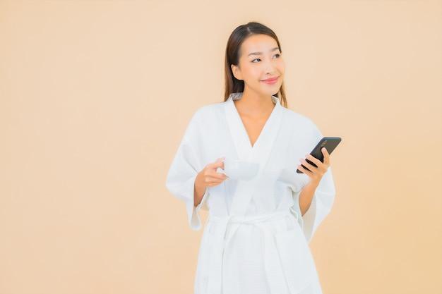 베이지 색에 스마트 휴대 전화를 사용 하여 세로 아름 다운 젊은 아시아 여자 무료 사진