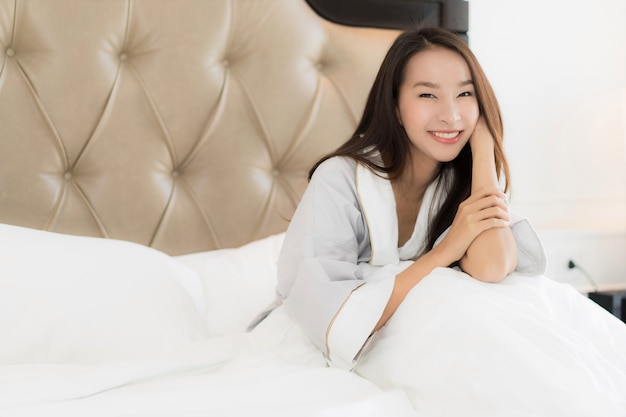 Portrait beautiful young asian woman wake up with happy and smile on bed in bedroom interior Free Photo