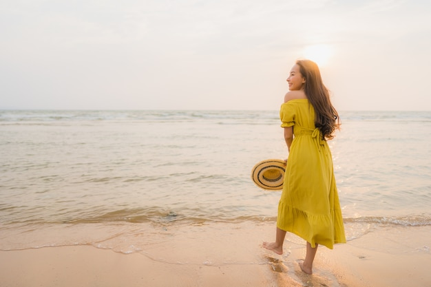 Portrait beautiful young asian woman walk on the beach and sea ocean with smile happy relax Free Photo