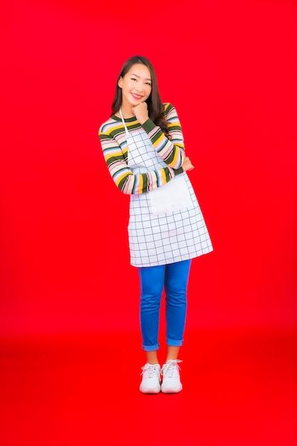 肖像画美しい若いアジアの女性は赤い壁にエプロンを着用 無料写真