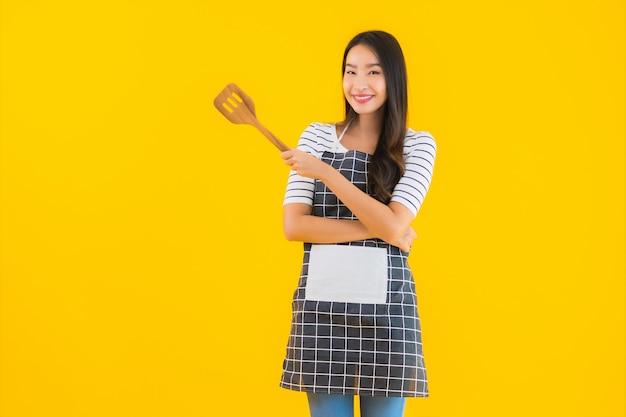 肖像画の美しい若いアジアの女性は黒い鍋とヘラでエプロンを着用します。 無料写真
