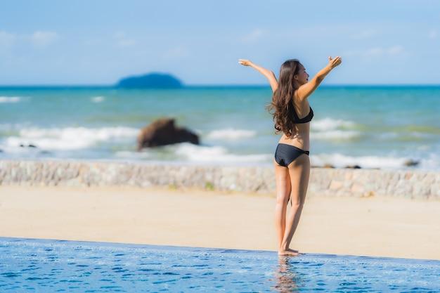肖像画美しい若いアジア人女性はホテルのリゾート地のスイミングプールの周りビキニを着るほぼ海海ビーチ 無料写真