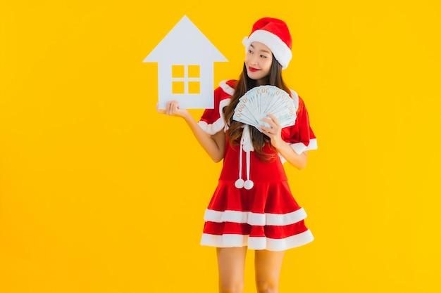 肖像画の美しい若いアジア女性はクリスマスの服を着て、帽子は家の家の看板を表示 無料写真