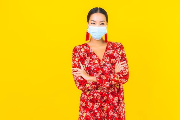 Маска носки женщины портрета красивая молодая азиатская для защиты вируса короны или covid19 на желтой стене Бесплатные Фотографии