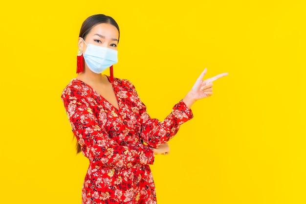La bella giovane donna asiatica del ritratto indossa la maschera per proteggere il virus corona o covid19 sulla parete gialla Foto Gratuite