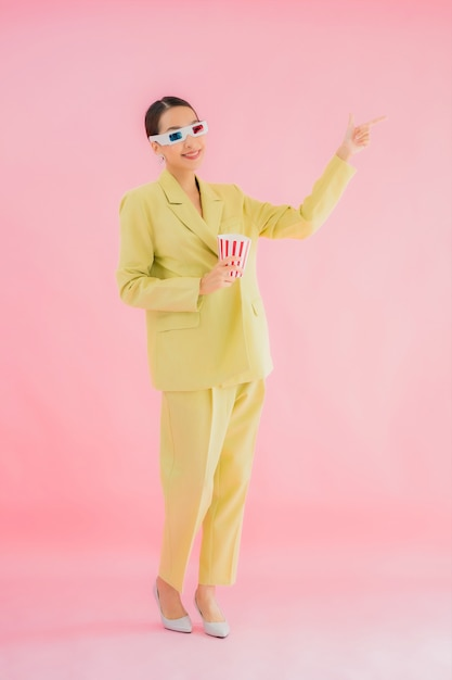 3 d眼鏡とポップコーンの色で映画を見る準備ができての肖像若いアジア女性 無料写真
