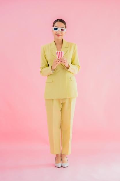 Ritratto bella giovane donna asiatica con occhiali 3d e popcorn pronti per guardare film a colori Foto Gratuite