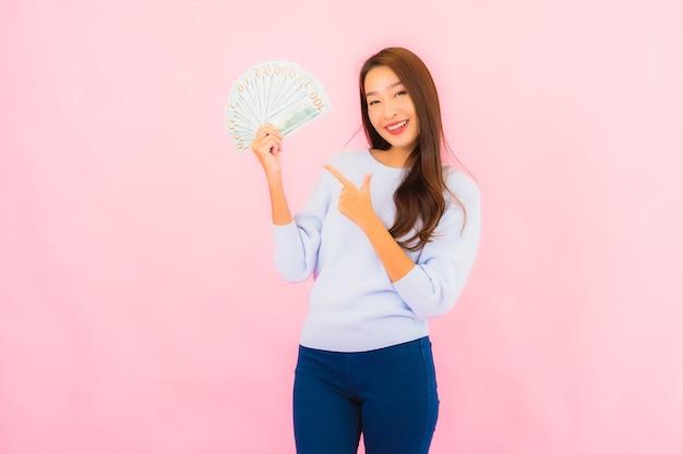 Женщина портрета красивая молодая азиатская с большим количеством наличных денег и денег на стене розового цвета Бесплатные Фотографии