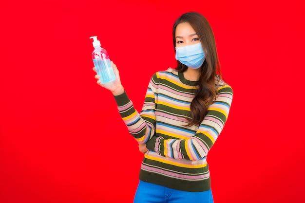 Женщина портрета красивая молодая азиатская с гелем спирта на красной изолированной стене Бесплатные Фотографии
