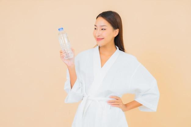 ベージュの飲み物のボトルウォーターと肖像画美しい若いアジアの女性 無料写真