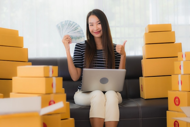 Portrait of beautiful young asian woman with cardboard parcel boxes and money Free Photo
