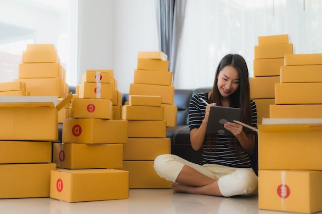 Portrait of beautiful young asian woman with cardboard parcel boxes Free Photo
