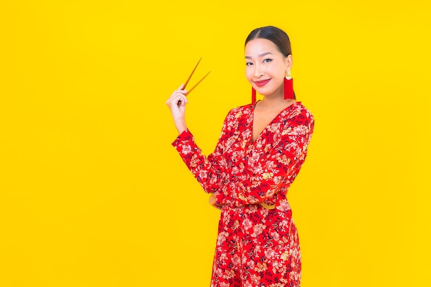색상 격리 된 벽에 젓가락으로 초상화 아름 다운 젊은 아시아 여자 무료 사진